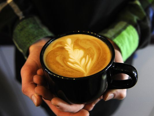 Calvin Hines holds a latte from River Road Coffee House. Photo: Sara C. Tobias/The Advocate